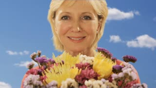 woman smelling bouquet of flowers with sky background