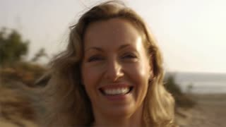 Woman spinning around on beach.