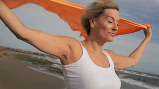 Woman standing on windy beach with orange scarf.