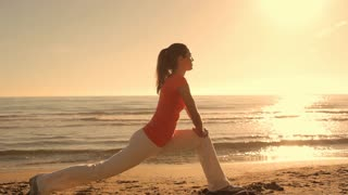 Woman stretching on beach in sunset.