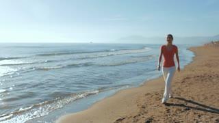 Woman walking on beach in sunset.