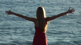 woman with arms outstretched to the sea