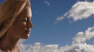 Woman's face with clouds in the background.