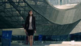 Young businesswoman using smartphone outside office building