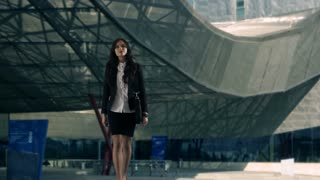 Young businesswoman using smartwatch outside office building