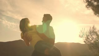 Young couple dancing and twirling overlooking mountain in sunset.