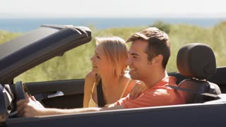 young couple driving convertible car by beach