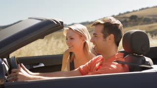 young couple driving convertible car in countryside