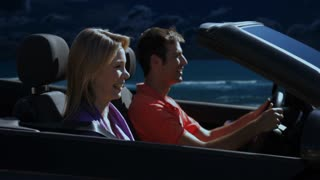 young couple driving convertible car in moonlight