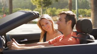 young couple driving convertible car in town