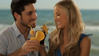 young couple having drinks by sea