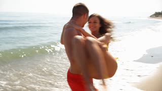 Young couple hugging and twirling on beach