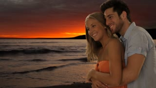 young couple hugging on beach in sunset