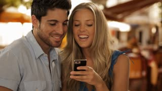 young couple in cafe looking at phone