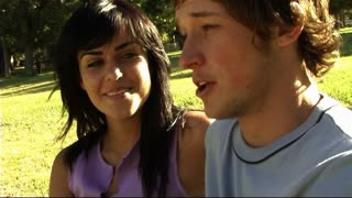 Young couple in park eating ice-cream