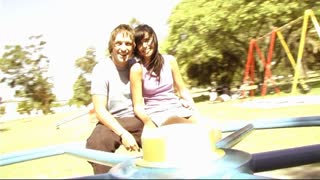 Young couple in park on roundabout