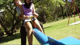 Young couple in park on seesaw