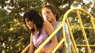 Young couple in park on slide