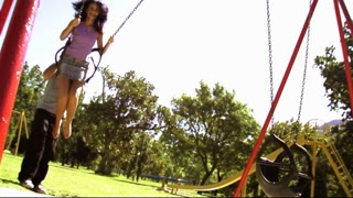Young couple in park on swing
