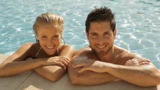 young couple laughing at side of pool