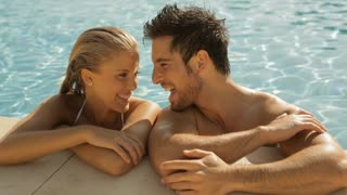 young couple laughing with drinks at side of pool