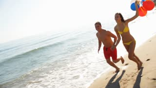 Young Couple on beach running with balloons