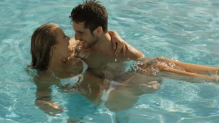 young couple playing and laughing in pool