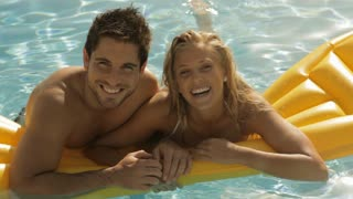 young couple playing and laughing on lilo in pool