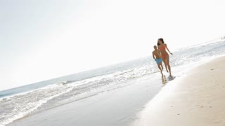 young couple running and chasing on beach