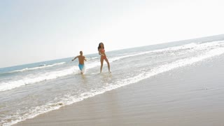 young couple running and chasing on the beach