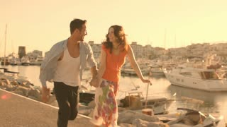 Young couple running  and dancing by marina in sunset.