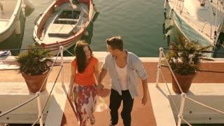 Young couple running up steps at marina.