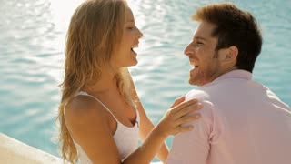 young couple sitting by pool