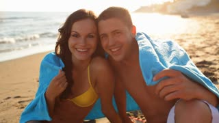 Young couple sitting on beach with blue towel