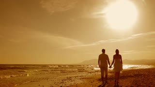 young couple standing on beach in sunset