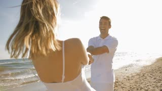 young couple twirling on beach