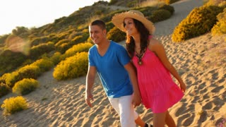 Young couple walking in dunes in sunset