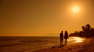 Young couple walking on beach in sunset