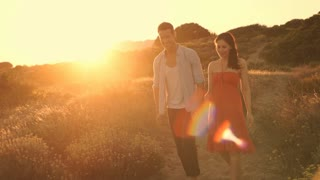 Young couple walking on sand dunes in sunset.
