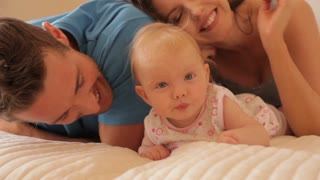 Young family with baby on bed indoors.