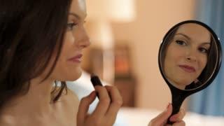 young girl in bedroom applying lipstick in mirror