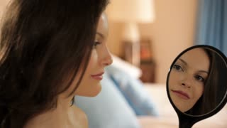 young girl in bedroom smiling into mirror