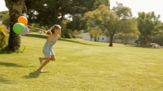 young girl running with balloons in park