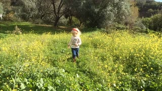 Young girl walking to camera in flower meadow