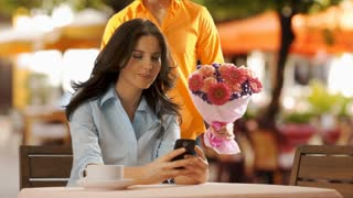 Young man bringing flowers to young woman in cafe .