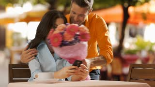 Young man bringing flowers to young woman in cafe.