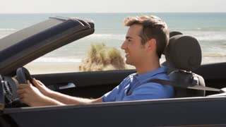 young man driving convertible car by beach