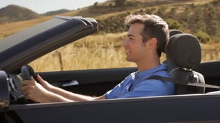 young man driving convertible car in countryside