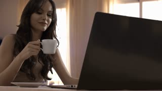 Young woman drinking coffee and using laptop and smartphone at home