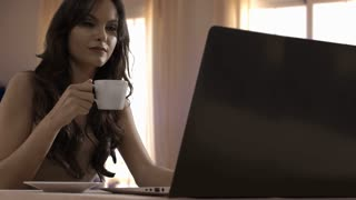 Young woman drinking coffee and using laptop at home